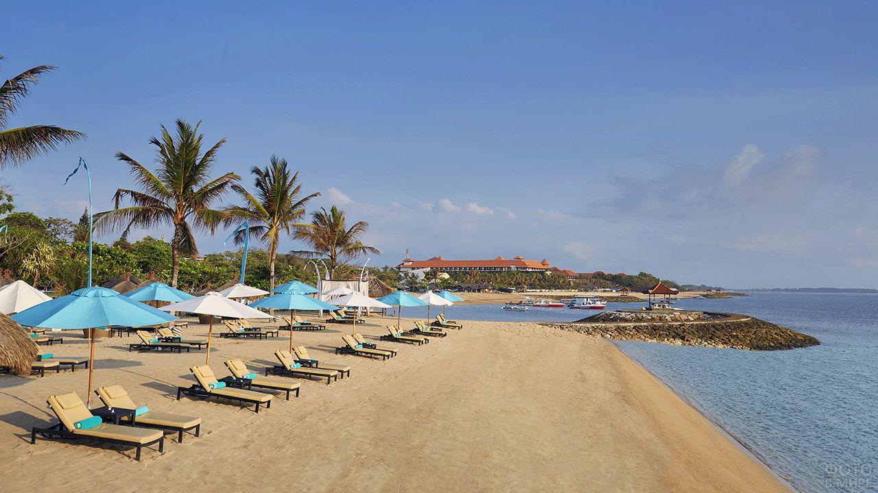 Шезлонги под белыми и бирюзовыми зонтиками на пляже отеля на Бали