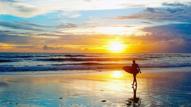 Силуэт сёрфера в лучах заката над морем на пляже Куты