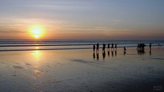 Силуэты людей на фоне заката на пляже Куты на Бали