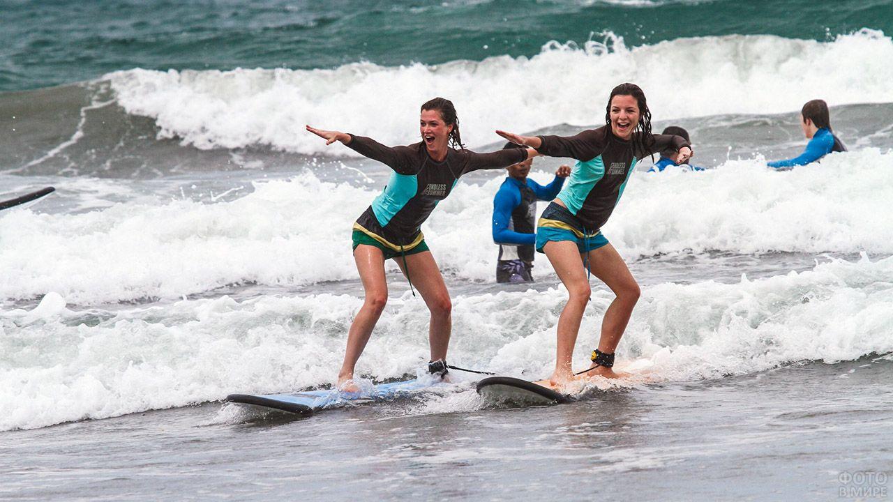 Сёрфингистки позируют в пене пляжа на Бали