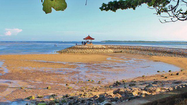 Солнечный пляж с индонезийской беседкой на Бали