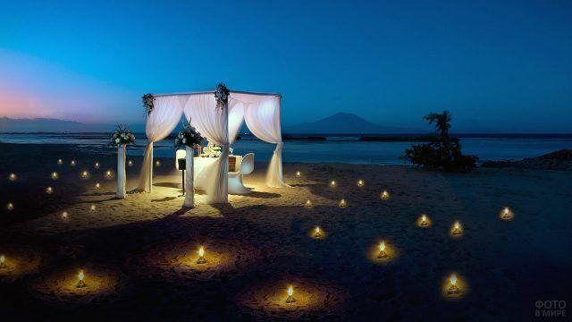Столик для романтичного ужина в вечерних огнях на пляже Бали