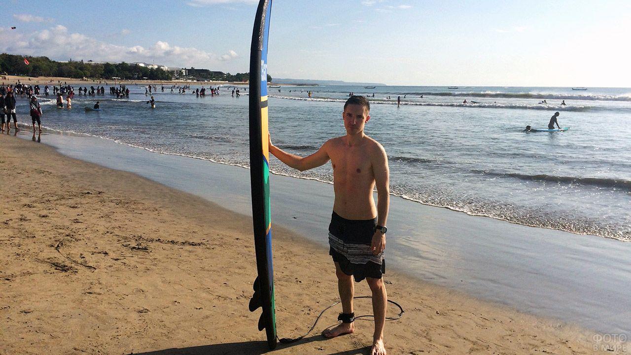 Турист с доской для сёрфинга позирует на пляже Куты на острове Бали