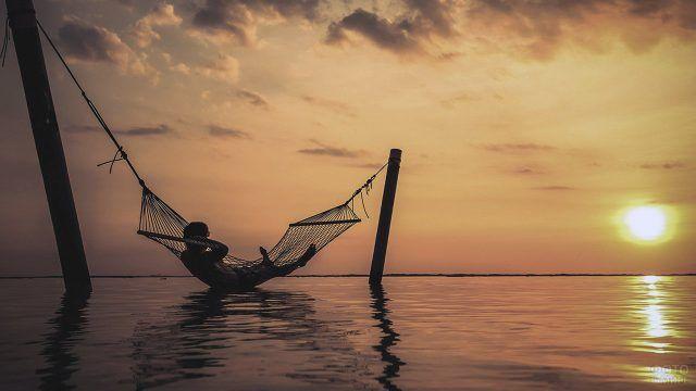 Турист в гамаке над водой в лучах заходящего солнца на куроте острова Бали