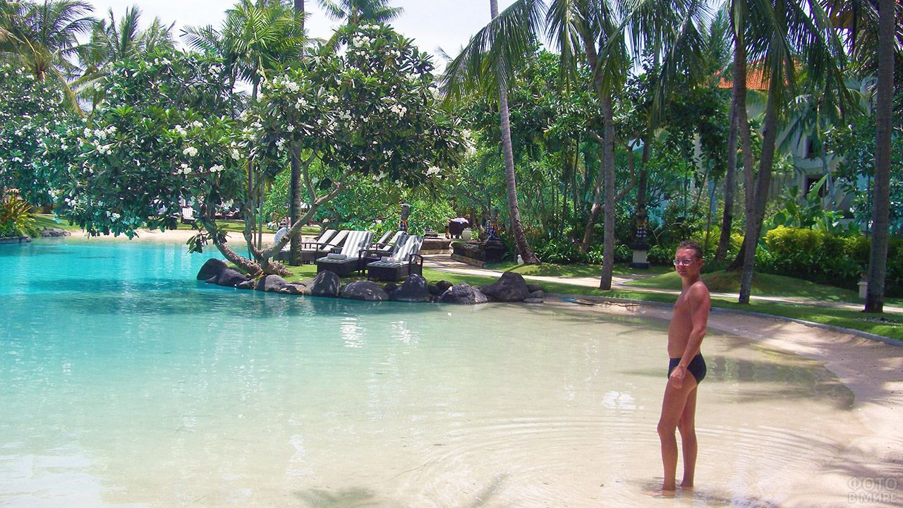 Турист в тени пальм на мелководье у отеля на острове Бали