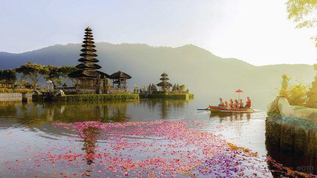 Туристический вид Бали с индуистскими храмами и лепестками розовых цветов на воде