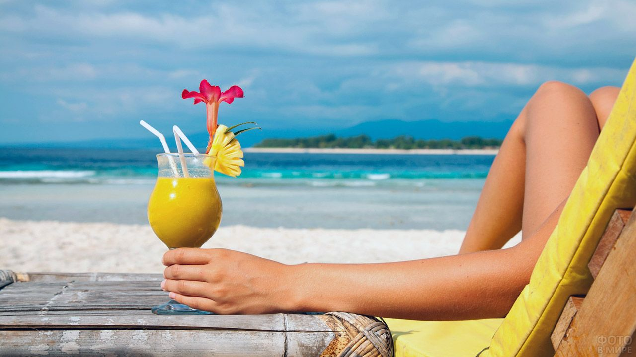 Туристка в шезлонге с тропическим коктейлем на пляже Бали