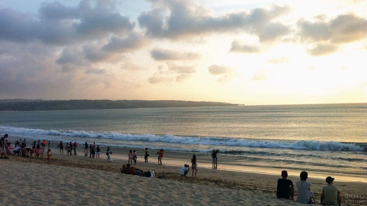 Туристы на вечернем пляже в лучах заходящго солнца на Бали