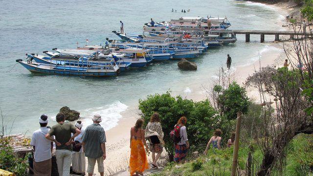 Туристы спускаются из парка Бали Барат к пирсу с катерами