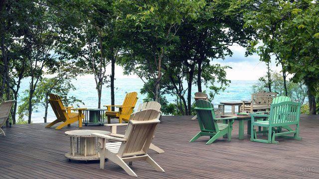 Веранда со столиками для туристов у пляжа на острове Менджанган