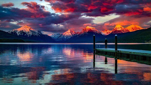 Человек на пирсе и пурпурный закат над озером в горах