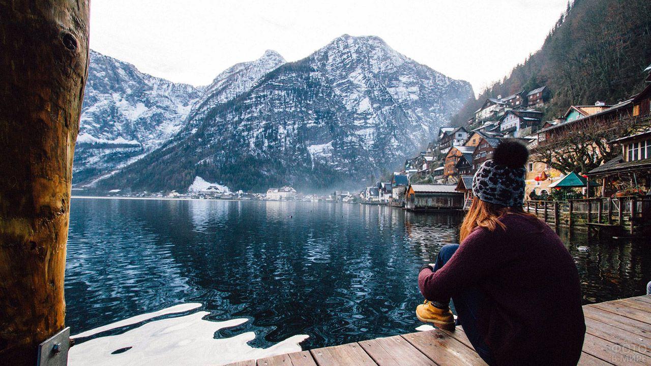 Девушка на пирсе туристической деревушки у высокогорного озера