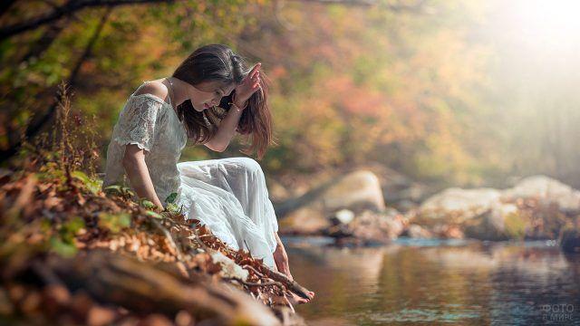 Девушка в белом платье сидит на осеннем берегу над водой озера