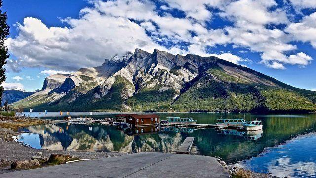 Летнее горное озеро с прогулочными лодками у причала