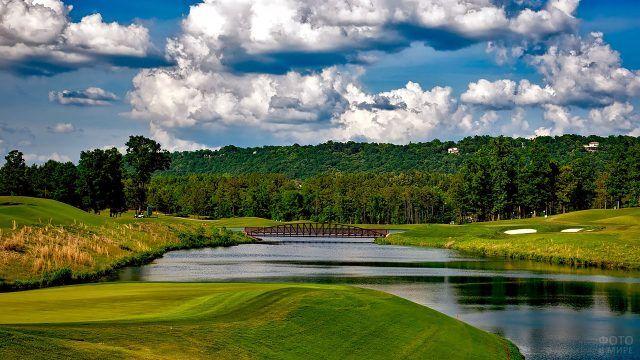 Мостик над озером в зелёном парке для гольфа