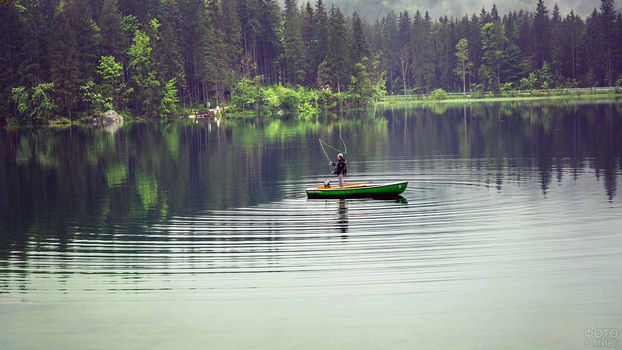 Рыболов в лодке посреди лесного озера