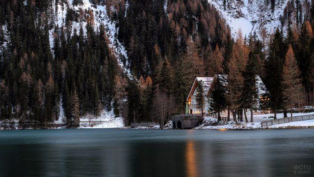 Шале под деревьями на берегу зимнего горного озера