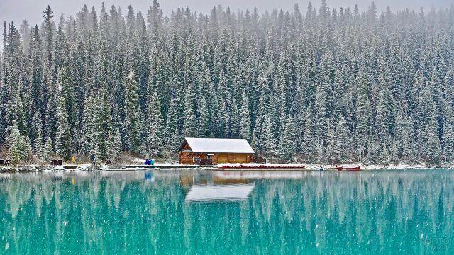 Снегопад над бирюзовым озером с лодочной станцией у старого леса