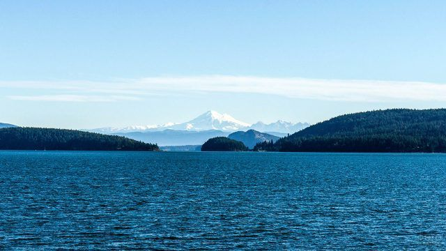 Тёмно-синее озеро и хвойный лес на фоне снежной вершины горы
