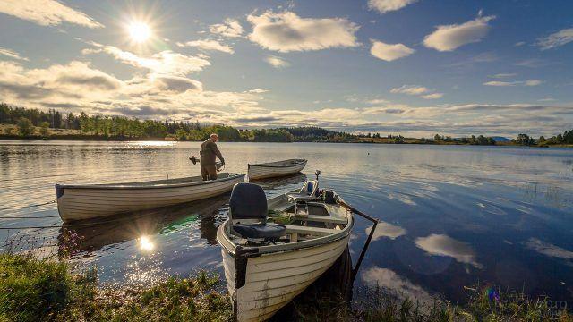Три рыболовные лодки у пологого берега озера