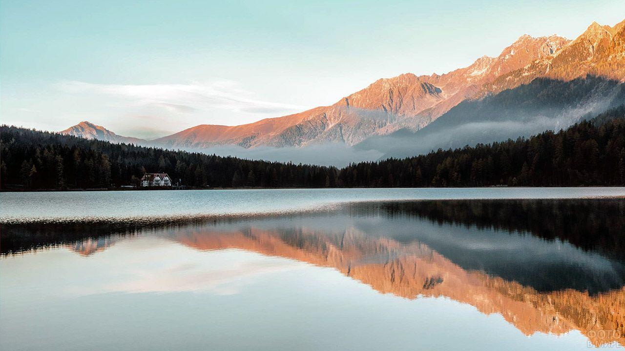 Туманный лес и горы в лучах восхода отражаются в серебристом зеркале озера