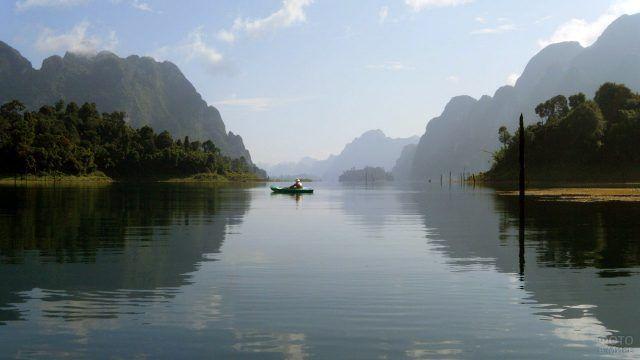 Турист в резиновой лодке посреди горного озера