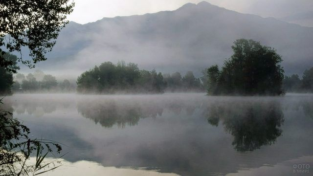 Утренний туман над горным озером и лесом на берегу