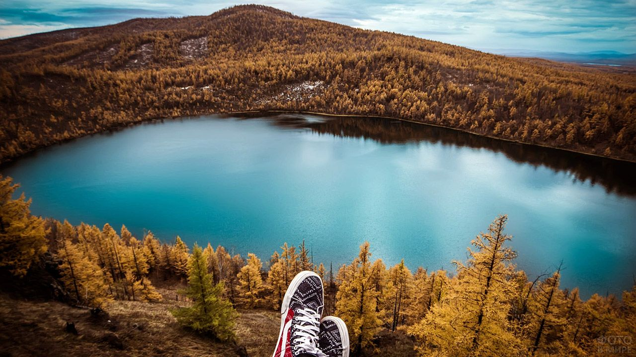 Вид на горное озеро с вершины лесистого холма