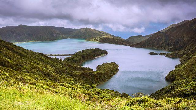 Вид с вершины зелёного холма на горное озеро