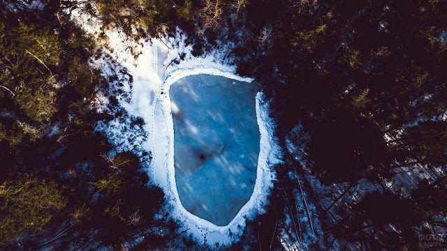 Вид сверху на замёрзшее лесное озеро с заснеженными берегами