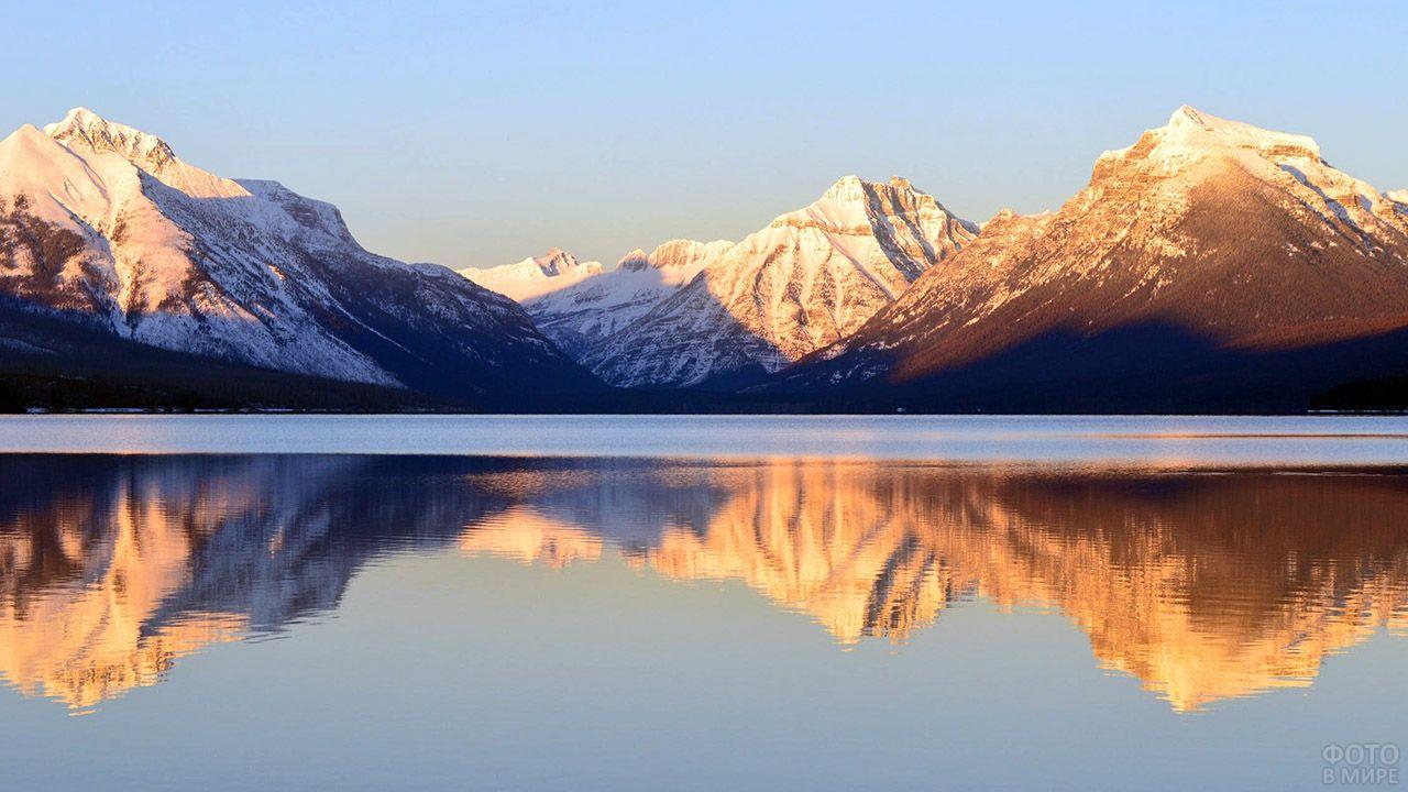 Восход над снежными вершинами гор отражающихся в озере