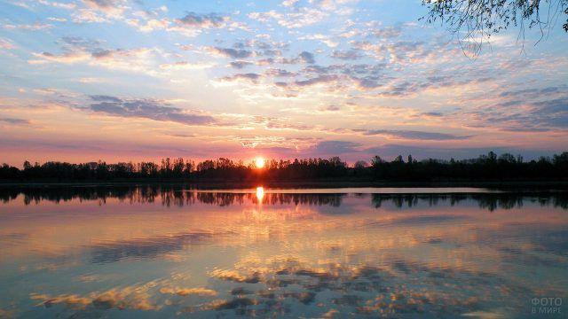 Восходящее солнце и розовеющие облака отражаются в воде лесного озера