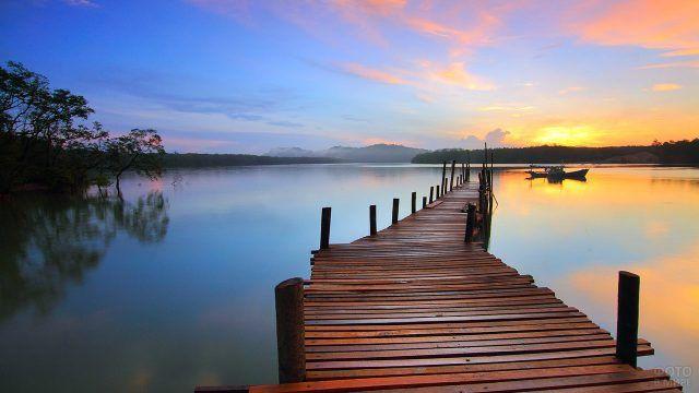 Закат над озером с деревянным помостом