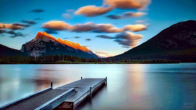 Закатное небо над горным озером с деревянным пирсом у берега