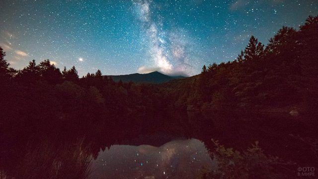 Звёзды в ясном ночном небе отражаются в лесном озере