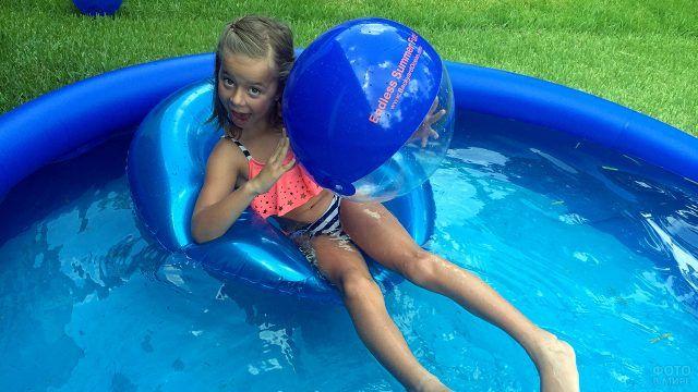 Девочка кривляется на камеру сидя в надувном бассейне на даче