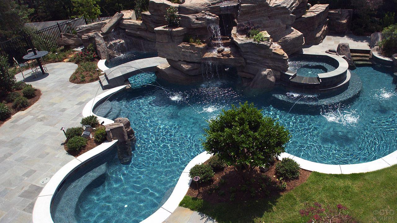 Дизайнерский бассейн с фонтанами, водопадом и мостиком в углу сада