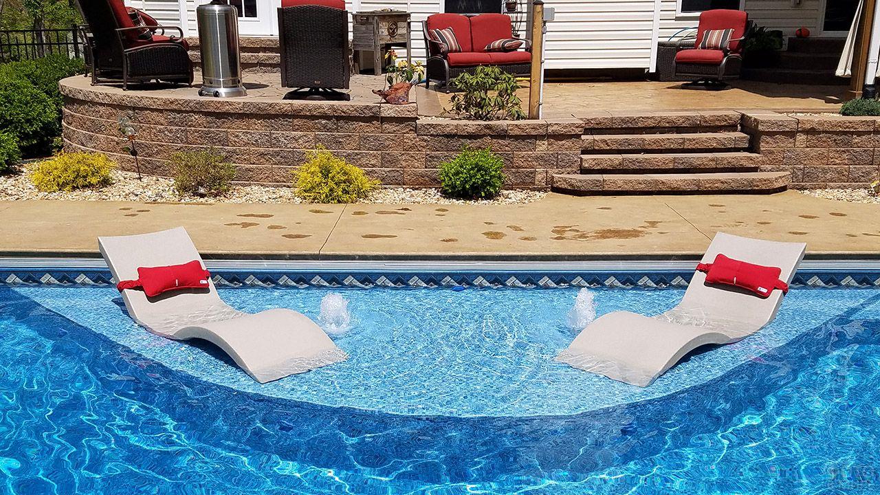 Футуристичные шезлонги на мелководье двухуровнего бассейна у веранды дома