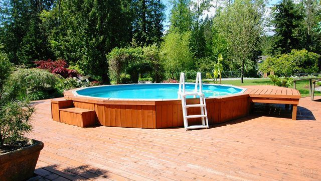 Каркасный бассейн с деревянным подиумом на дачном участке