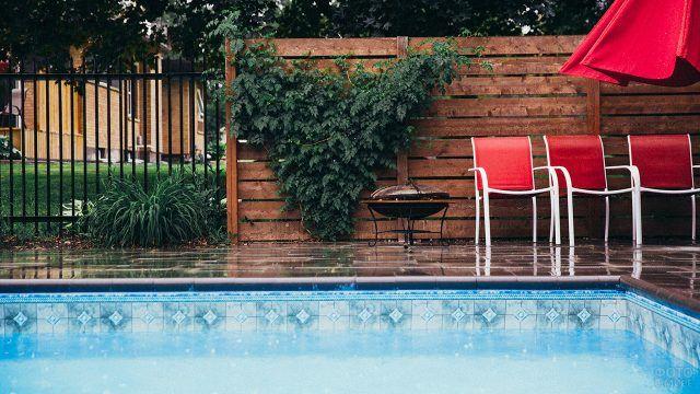 Красные стулья и жаровня-гриль у бассейна на заднем дворе загородного дома