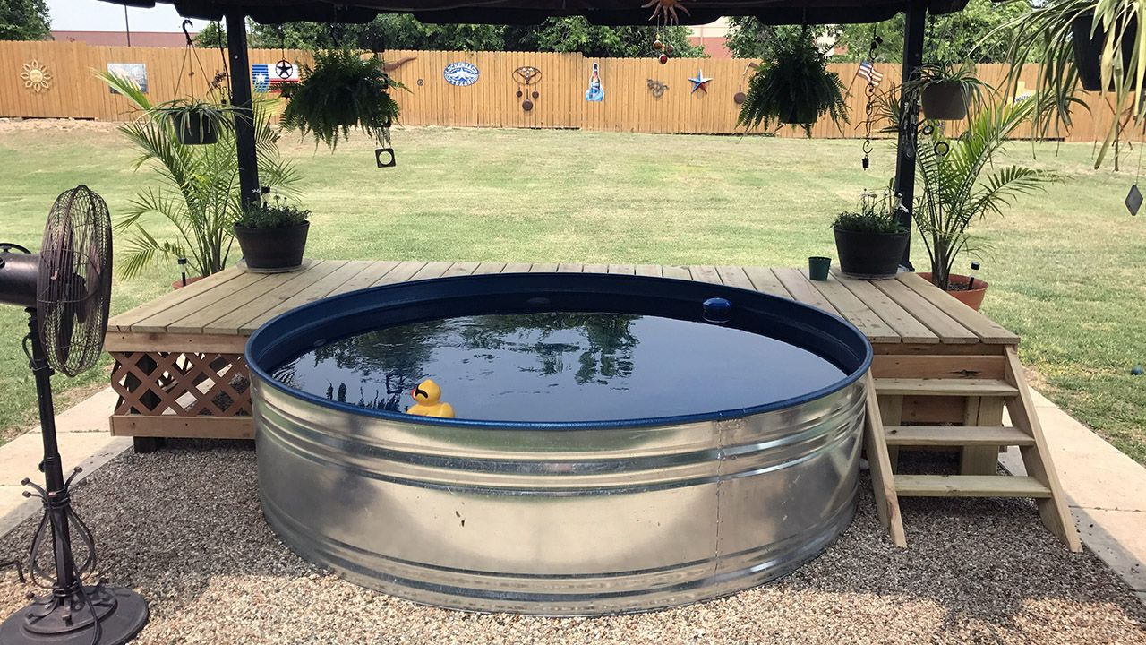 Круглый каркасный бассейн под тентом на солнечной лужайке загородного дома