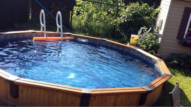 Круглый каркасный бассейн с деревянными бортами на солнечной лужайке