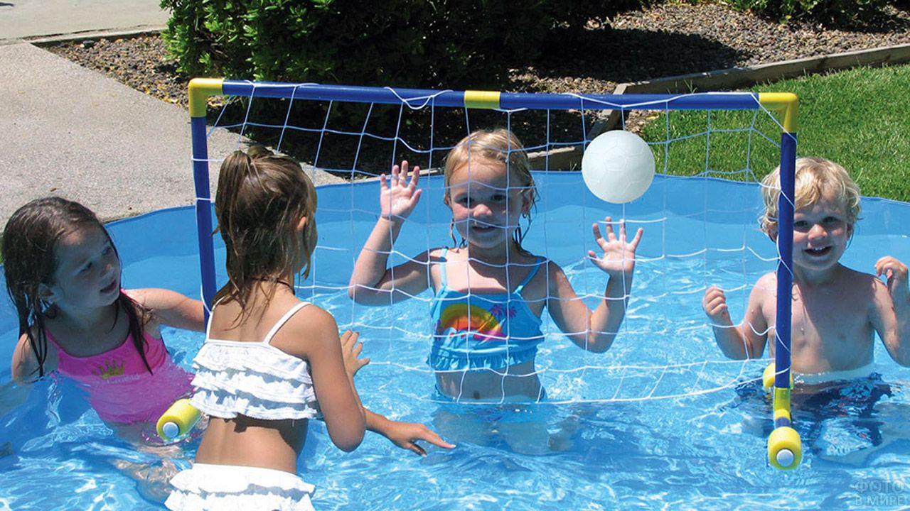 Малыши играют в мяч в маленьком бассейне в саду