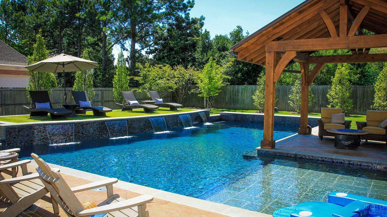 Небольшой дизайнерский бассейн с водопадами и патио на заднем дворе дома