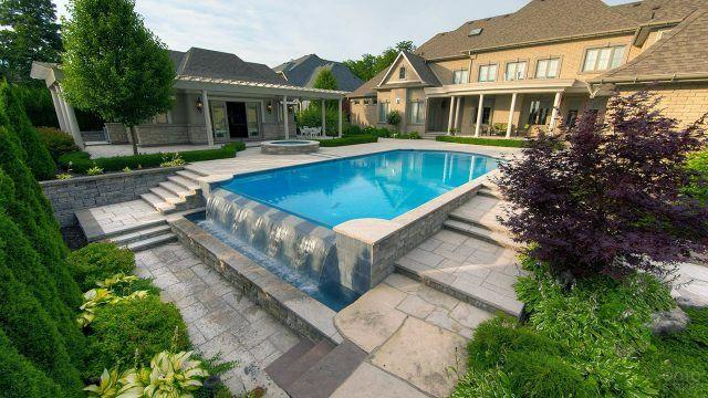Прямоугольный бассейн и ландшафтный дизайн с водопадом на заднем дворе виллы