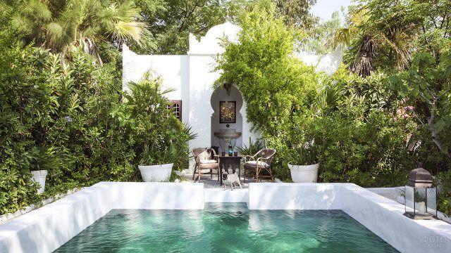 Прямоугольный бассейн с высокими белыми бортиками в пышном зелёном саду