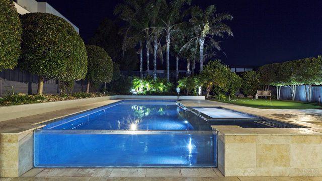 Роскошный бассейн с прозрачным бортиком в ночном саду