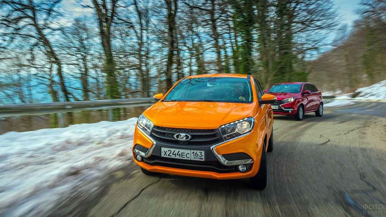 Оранжевая и красная Лады Икс Рей мчатся по загородной зимней дороге