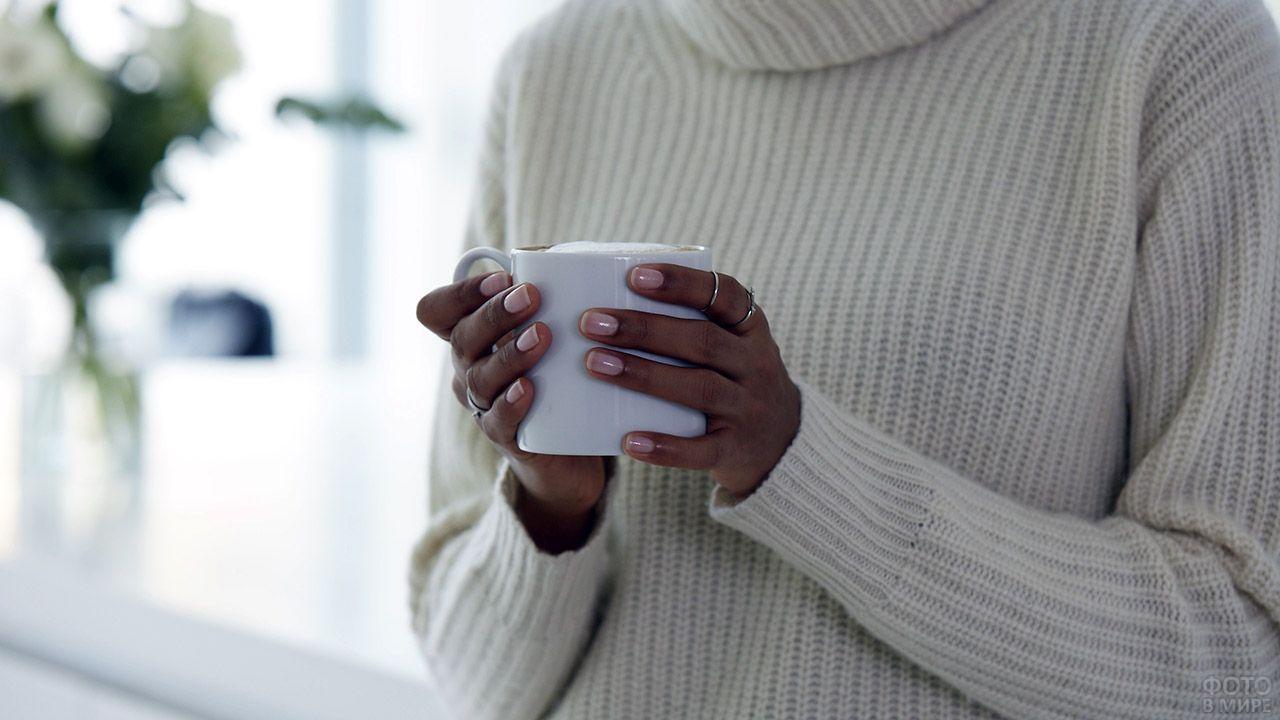 Негритянка с ухоженными ногтями держит белую кружку в руках