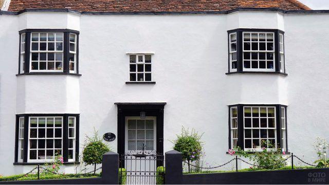 Белый фасад двухэтажного дома с чёрными рамами окон в эркерах
